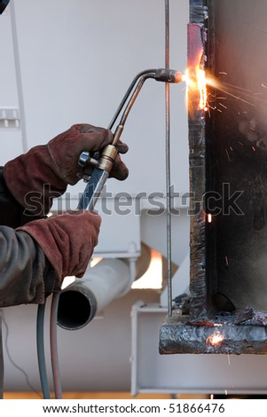 welder cutting metal in factory using acetylene torch - stock photo