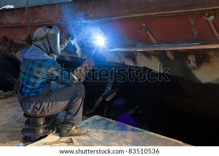 Welder in a protective mask when working. - stock photo