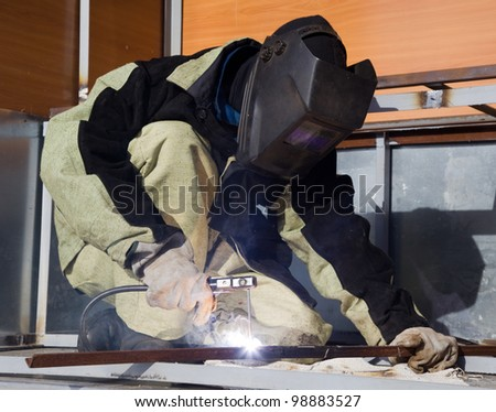 Welder in a special suit, while working in direct sunlight - stock photo