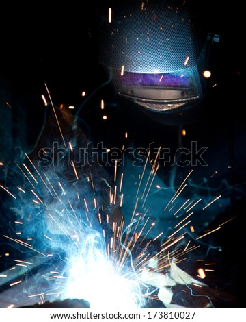 Welder in action with bright sparks. Construction and manufacturing theme. - stock photo