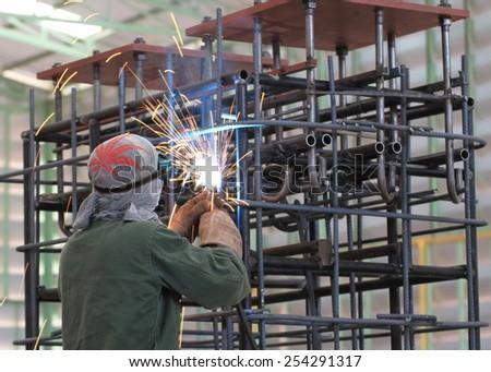 welder is welding steel frame in factory - stock photo