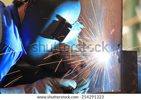 welder is welding steel plate with all safety - stock photo