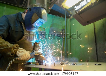 Welder man worker welding with electrode metal product at factory workshop - stock photo