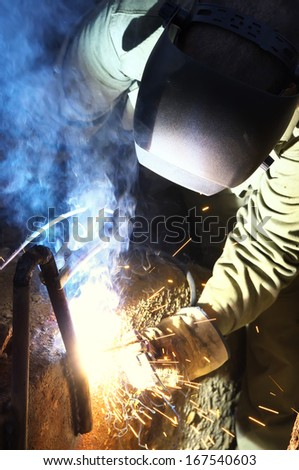 Welder on the industrial workplace. Construction and manufacturing - stock photo