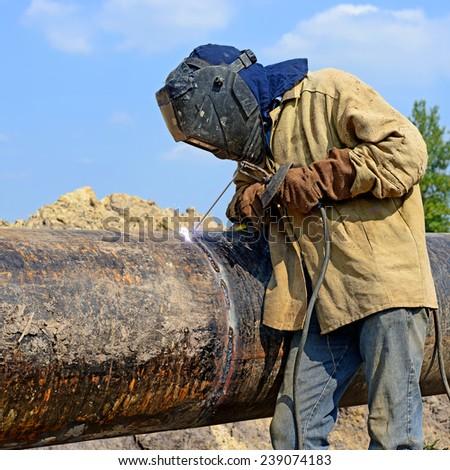 Welder on the pipeline repairs - stock photo