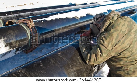 welder performs welding of pipe insulation on the pipeline route high pressure in winter conditions - stock photo