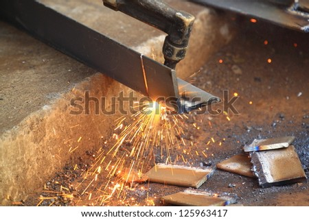 Welder uses torch to make sparks - stock photo