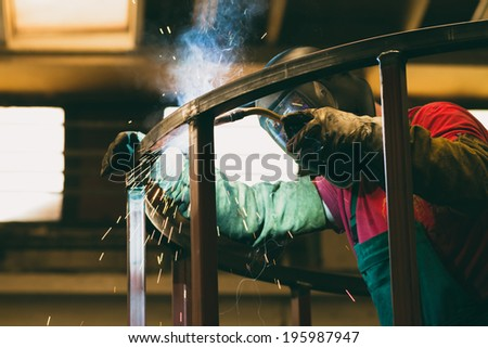 welder uses torch to make sparks during manufacture of metal equipment - stock photo