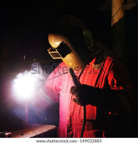 Welder uses torch to make sparks to weld metal equipment - Square Format - stock photo