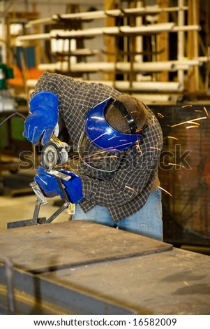 Welder using a grinder to smooth a piece of metal.  Authentic and accurate content depiction in compliance with industry code and safety standards. - stock photo
