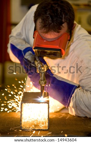 Welder using an acetylene torch to cut through a metal box.  Focus on the torch.   All work depicted is accurate and in compliance with industry code and safety regulations. - stock photo