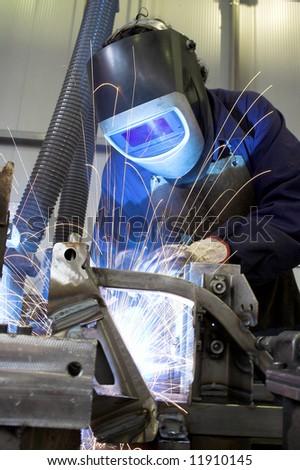 Welder welding a car part - stock photo