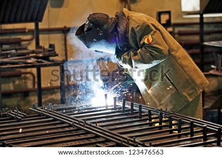 Welder welding pipe grid - stock photo