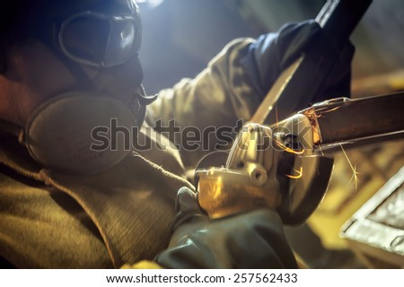Welder welding seams cleans angle grinder. - stock photo
