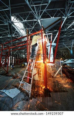 Welder welds steel frame standing on stepladder - stock photo