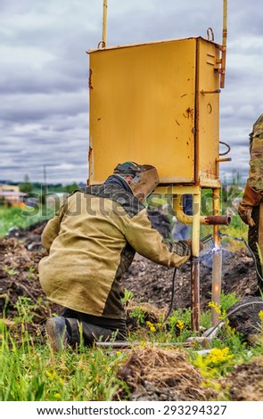 Welder with mask soldering pipe outdoor in countryside - stock photo