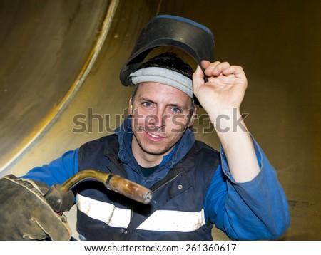 welder with mig/ mag welding gun in his hand, lifting his welding mask with his other hand - stock photo