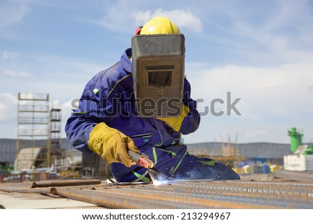 welder with protective equipment welding steel bars outdoors - stock photo