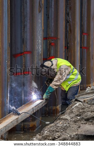 Welder with protective equipment welding steel beams in trench filled with water at construction site. Made with selective focus. - stock photo