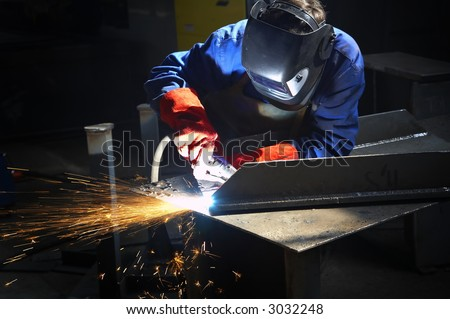 welder with protective mask welding/finishing metal and sparks - stock photo