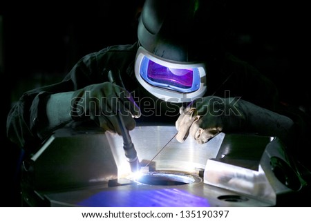 Welder, working on the center ring of a large metal part - stock photo