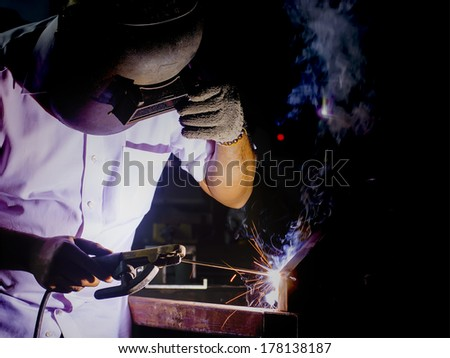 welder working with protective mask welding metal and sparks - stock photo