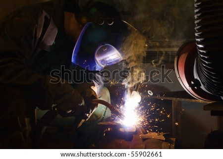 Welder working with welding helmet, sparks and smoke around him - stock photo