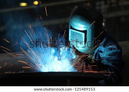 welders with protective mask in the factory - stock photo