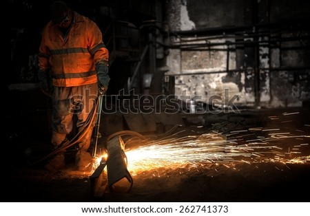 Welding man with sparks in a factory - stock photo