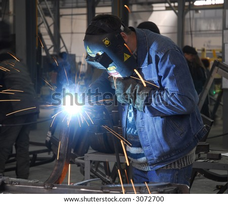 welding operator holding his mask - stock photo