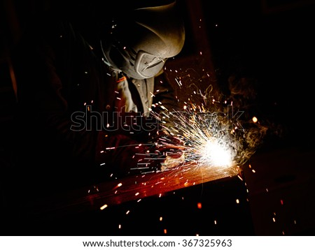 Welding sparks and welder - stock photo