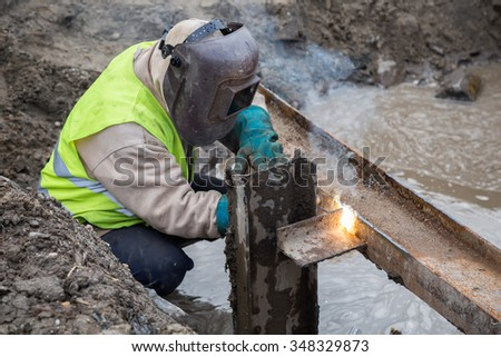 Welding steel beams in trench filled with water at construction site. - stock photo
