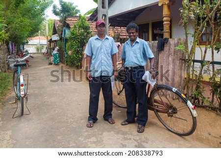 WELIGAMA, SRI LANKA - MARCH 8, 2014: Two postmen delivering post to local people. Sri Lanka Posts has been in existence for more than 209 years and employs more than 17,000 employees. - stock photo