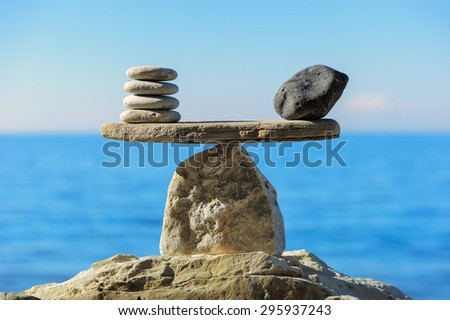 Well-balanced of pebbles on the top of sea boulder - stock photo