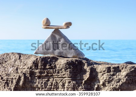 Well-balanced stack of pebbles on the sea boulder - stock photo