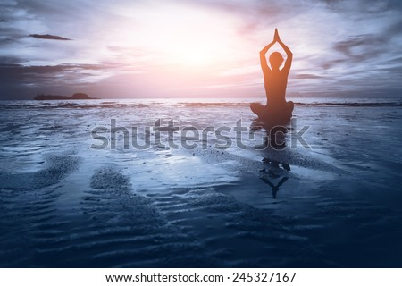 well being concept, beautiful sunset on the beach, woman practicing yoga - stock photo