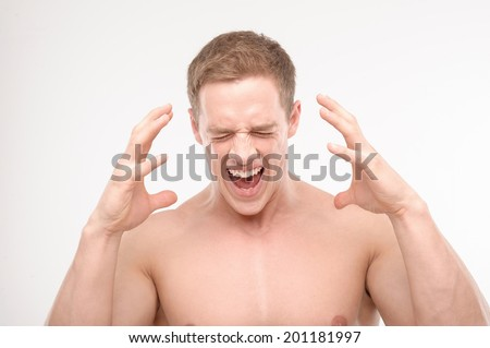 Well built muscular shirtless athletic man screaming with arms raised isolated on white. - stock photo