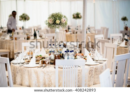 Well-decorated table in the wedding tent - stock photo