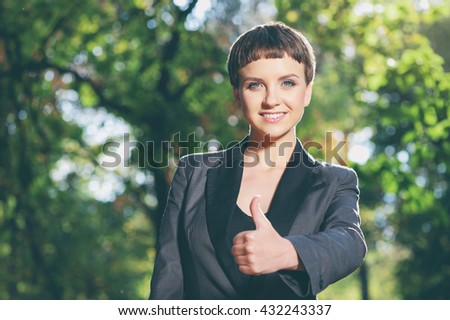 Well done! Beautiful young caucasian woman in formalwear showing her thumb up and smiling while standing outdoors - stock photo