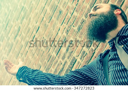 Well dressed bearded man lifts his hand to a higher power - stock photo