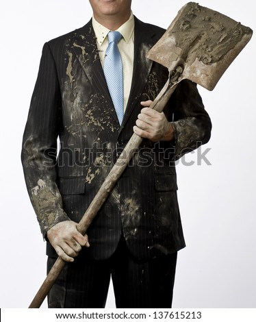 Well dressed business man holding a shovel with dirty clothes. Relationship between blue collar and white collar workers - stock photo