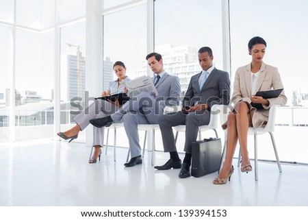 Well dressed business people sat together in a waiting room - stock photo