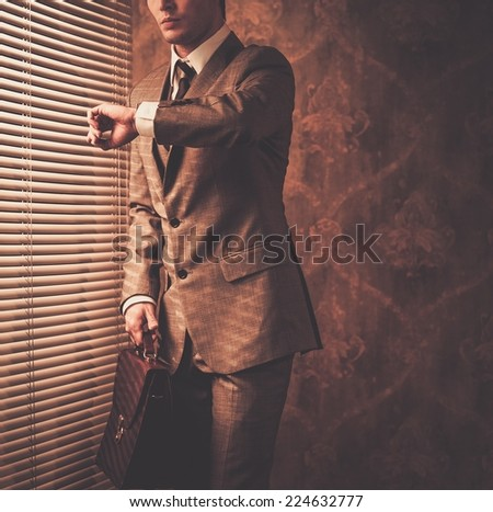 Well-dressed businessman looking at his watch - stock photo