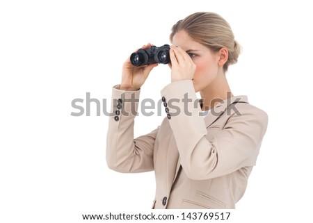 Well dressed businesswoman looking away with binoculars - stock photo