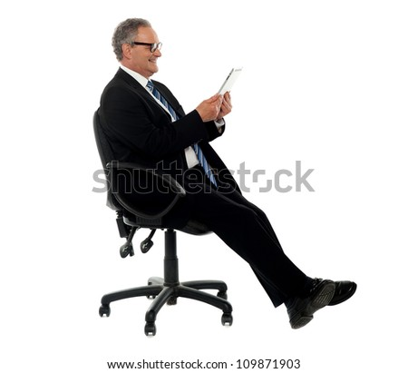 Well dressed corporate male holding wireless tablet, seated on chair, side pose - stock photo
