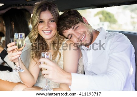 Well dressed couple drinking champagne in a limousine on a night out - stock photo