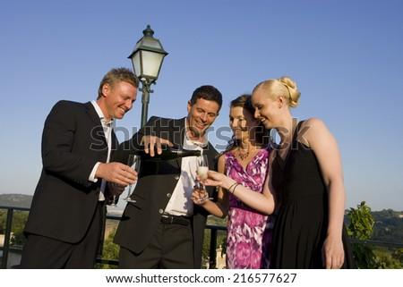 Well-dressed couples enjoying champagne on balcony - stock photo