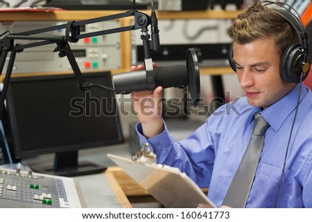 Well dressed focused radio host moderating sitting in studio at college - stock photo