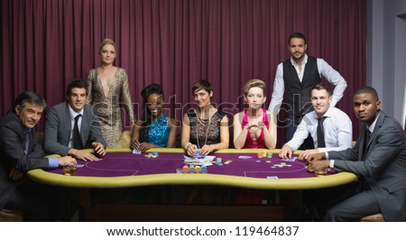 Well-dressed group at poker table in casino - stock photo