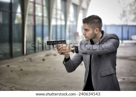 Well dressed handsome young detective or policeman or mobster standing in an urban environment aiming a firearm off to the left of the frame with a determined expression, side view - stock photo